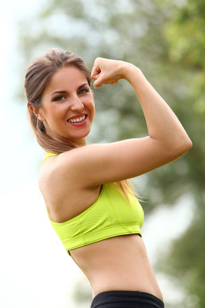 Beautiful caucasian woman working out in a park at sunny day photo