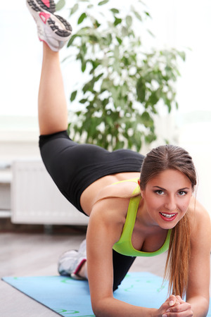 Beautiful caucasian woman working out at home on a yoga mat photo