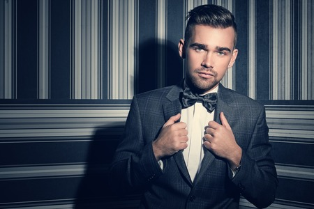 suit tie: Portrait of a handsome man in a suit and a tie who is posing over a striped background Stock Photo