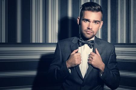 cabello corto: Retrato de un hombre guapo con un traje y una corbata que está posando sobre un fondo de rayas