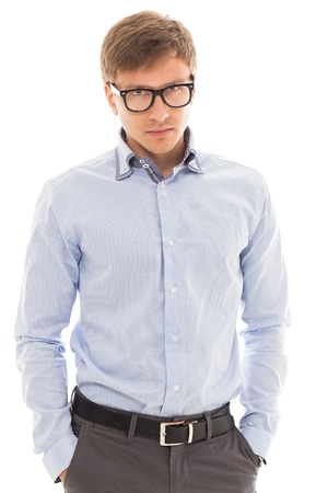20 24 years: Handsome man in a blue shirt and glasses holds his hands in pockets over a white background