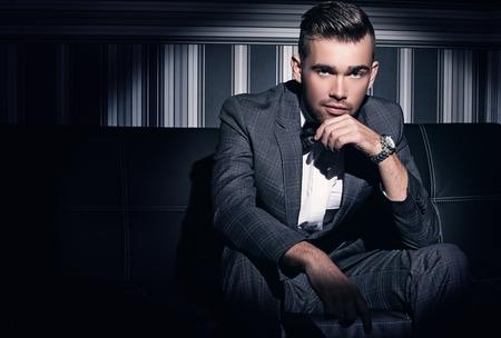 Porträt einer schönen Mann in einer Klage, die im Scheinwerferlicht auf einem gestreiften Hintergrund sitzt