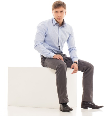 20 24 years: Handsome man in a shirt and trousers is sitting on a cube