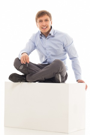 25 29: Handsome man in a shirt and trousers is sitting on a cube