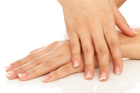 nailcare: Young woman hands with french manicure over white background
