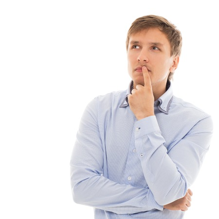 25 29 years: Handsome man in a blue shirt is thinking over a white background