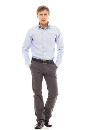 25 29: Handsome man in a blue shirt holds his hands in pockets over a white background