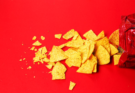 totopos: Potato chips on a red background Stock Photo