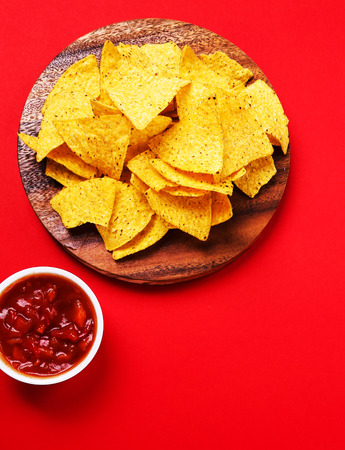 totopos: Potato chips with sauce on a red background Stock Photo