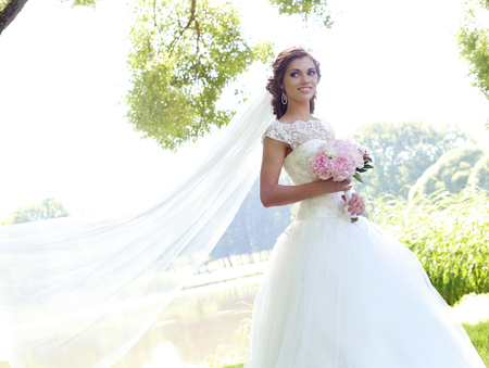 hairstyle: Beautiful bride with flower bouquet outdoor