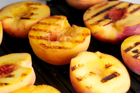 Food. Grilled peach on the table Imagens