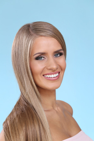 blonde yeux bleus: Woman with beautiful hair on a blue background Banque d'images