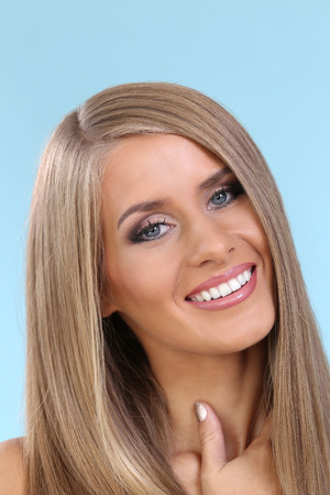 attractive gorgeous: Woman with beautiful hair on a blue background Stock Photo