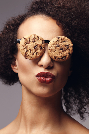 crazed: Weird, crazy. Woman with glasses made out of cookies Stock Photo