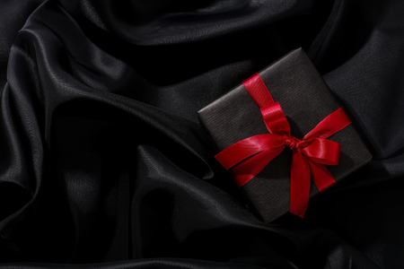 Christmas, New Year. Wrapped gift on a black background Stock Photo - 49173230