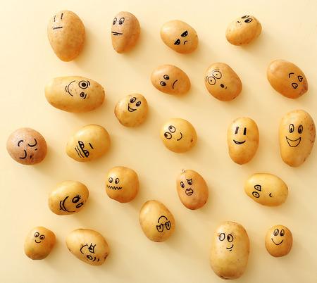アート。黄色の背景に面白いジャガイモ