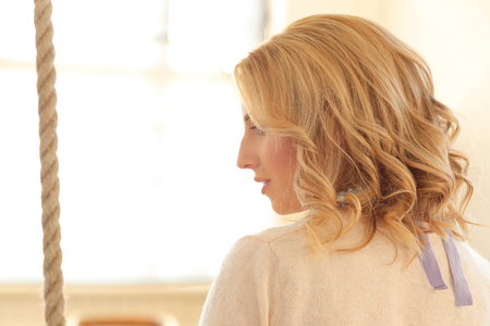 hair curly: chica rubia con el pelo rizado sentado en el columpio