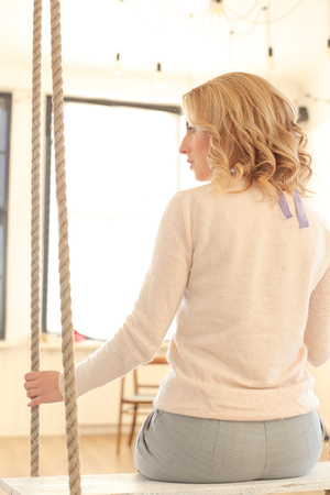 woman behind: Blonde girl with curly hair sitting on the swing