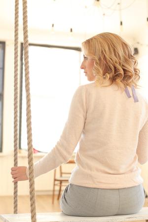 femme romantique: Jeune fille blonde aux cheveux bouclés assis sur la balançoire Banque d'images