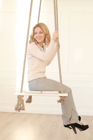 sitting up: Blonde girl with curly hair sitting on the swing