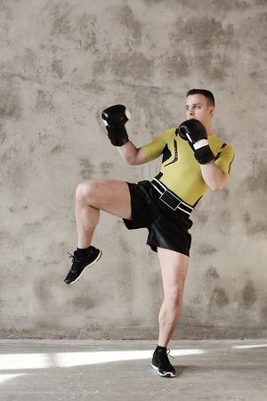 kickboxing: Handsome kickboxer on a grey background