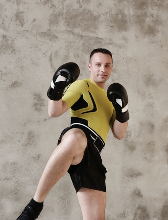 kickboxing: Handsome kickboxer on a grey background
