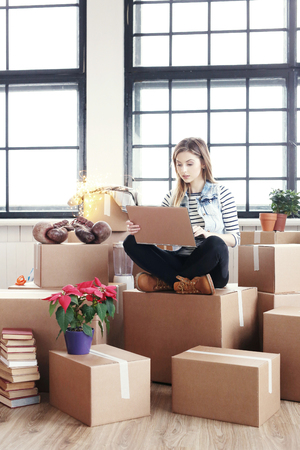 cardboard boxes: Cute girl during moving home Stock Photo