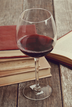 books on a wooden surface: Alcoholic drink. Red wine on the table
