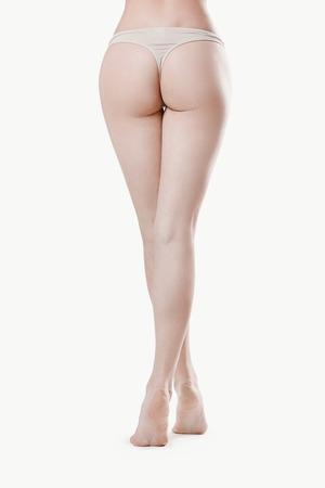 mujer desnuda de espalda: Spa de belleza. Piernas de la mujer sobre un fondo blanco Foto de archivo