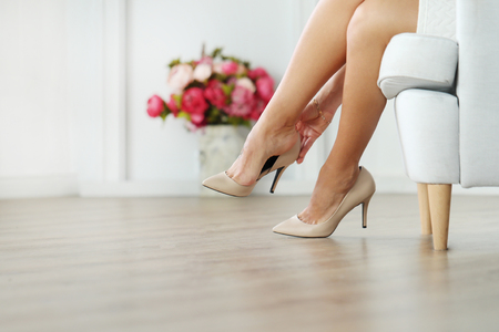 get dressed: Woman sitting on the armchair, while wearing heels