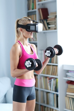 Workout. Woman with VR headset and dumbbels Stock Photo