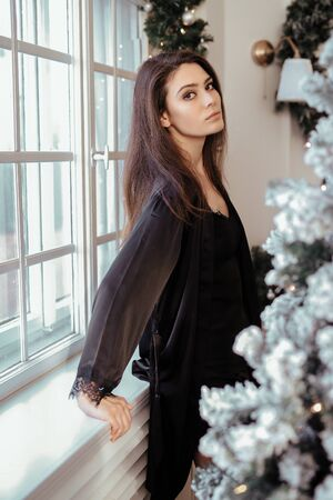 Woman by the Christmas tree 스톡 콘텐츠