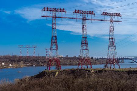 across: electricity pole across the reservoir in twilight