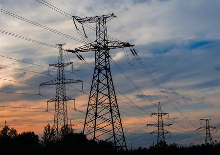 torres de alta tension: Las torres de electricidad y las líneas en la oscuridad al atardecer