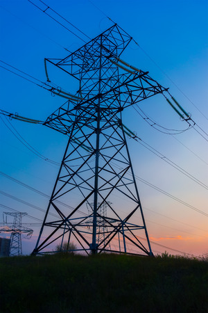 over voltage: storm at sunset over high voltage pylons Stock Photo