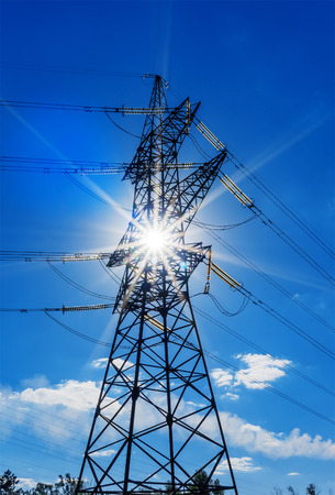 energy needs: high voltage electricity pylons against blue sky and sun rays