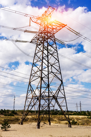 energy needs: through a mast of a high voltage cable for electricity, the sun shines. solar energy