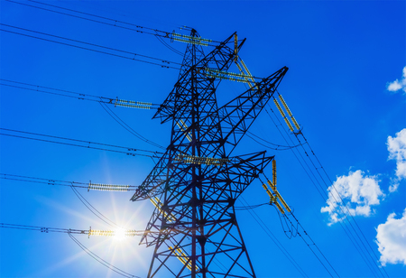 energy needs: power line silhouette against the blue sky with rays of sunlight