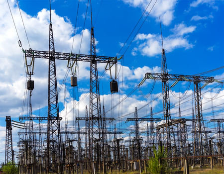 isolator: High Voltage Substation with towers on a background of blue sky with clouds Stock Photo