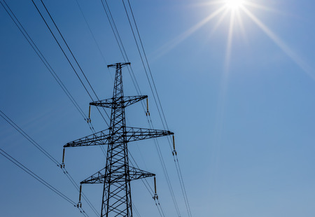 energy needs: a high voltage power pylons against blue sky and sun rays