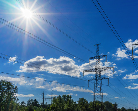 powerhouse: Power Line. pylon against a blue sky and sun Stock Photo