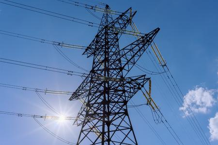 torres de alta tension: torres de alta tensión y líneas eléctricas, partes aisladas por el sol a través de contra el cielo azul Foto de archivo