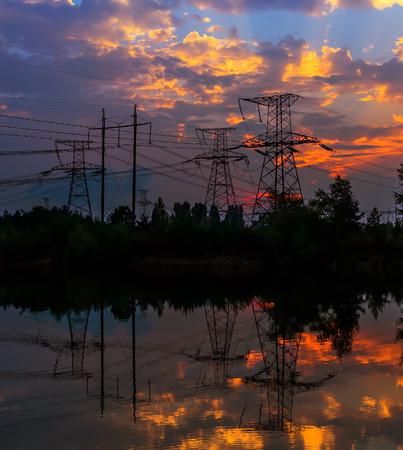 torres de alta tension: Electricity pylons and lines at dusk at sunset Foto de archivo
