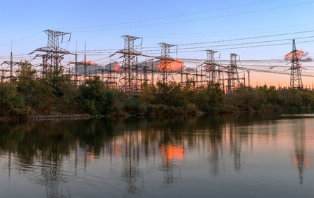isolator: Impression network at transformer station in sunrise, high voltage up to yellow sky take with yellow tone