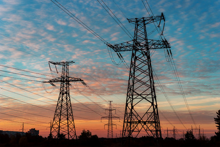 isolator: Electricity pylons and lines at dusk at sunset Stock Photo