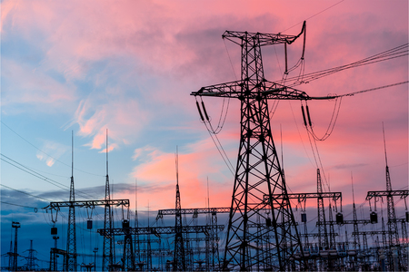 Electricity pylons and lines at dusk at sunset Stock Photo