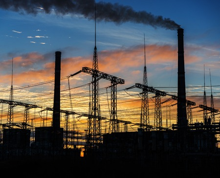 Smoke stacks at coal burning power plant, industrial silhouette