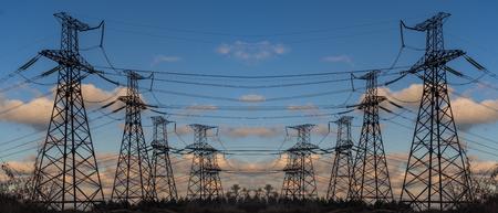 夕暮れ時の夏にパイロンと伝送の電力線 写真素材