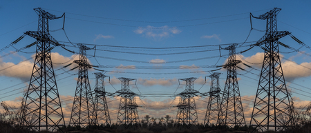 Pylon and transmission power line in summer at sunset Stockfoto