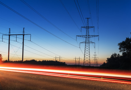 power transmission tower and lines at sunset tracks from cars Stock Photo